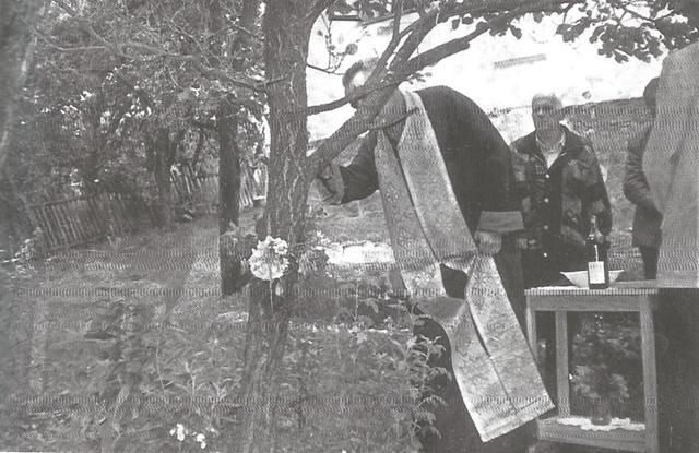 Foto iz arhive Narodnog muzeja u Čačku: Sveštenik adorira urezani krst vinom, selo Jezdina 2001. godine